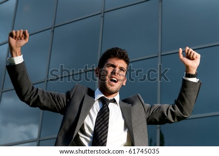 Young successful businessman celebrating a goal on a modern building background
