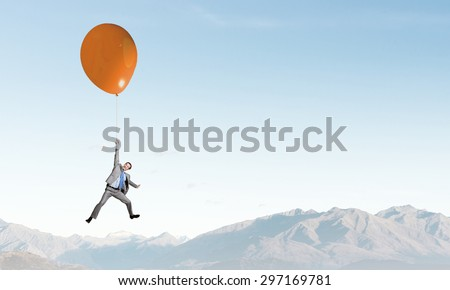 Young successful businessman flies on colorful balloon