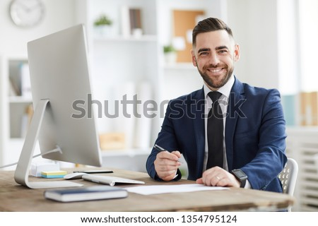 Young successful businessman in formalwear looking at you with smile while sitting by workplace in office