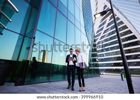 Young successful businessman in luxury suit is reading monthly report on portable digital tablet, while his female secretary with mobile phone and folder documents in hand is commenting her work stock photo