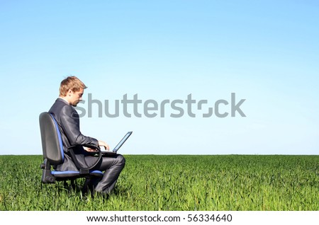 Young successful businessman, on the green meadow