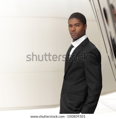 Young successful businessman posing in elegant suit against modern background with copy space