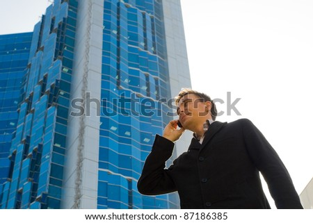 Young successful businessman talking on mobile phone opposite office building