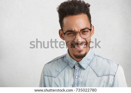 Young successful businessman with trendy hairdo, frowns face with pleasure, finds out about raising sales, recieves triumph at work, grins in camera. Studio shot of glad male student after session - Shutterstock ID 735022780