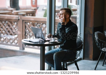 Young successful businessman working on a laptop while sitting in cafe. #1321239986
