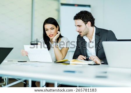 Young, successful businesswoman and a businessman looking at a paper while sitting at an office desk