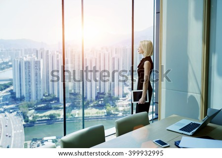 Young successful businesswoman with digital tablet in hand is thinking about future of her construction company, while is standing in modern office interior near window with Cityscape view. Copy space