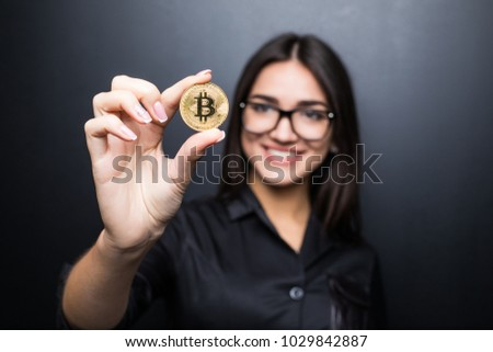 young successful confident woman with glasses holds a gold bitcoin in her hand