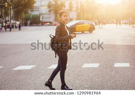 Young successful designer going to the office reading good news from friends on mobile phone and enjoying morning take away coffee - Image