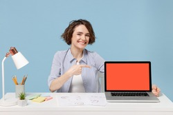 Young successful employee business woman in casual shirt sit work at white office desk point finger on pc laptop computer blank screen workspace area isolated on pastel blue background studio portrait