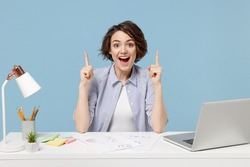 Young successful employee business woman in casual shirt sit work at white office desk with pc laptop point index finger overhead on workspace area isolated on pastel blue background studio portrait