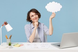 Young successful employee business woman in shirt sit work at white office desk with pc laptop empty blank Say cloud speech bubble promotional content prop up chin isolated on blue background studio