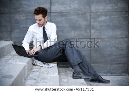 Young successful man working on laptop in outdoors.