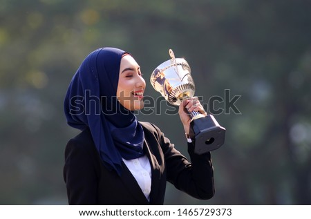 Young successful muslim girl with hijab celebrating her victory holding her winning trophy. Success business concept
