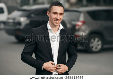 Young successful smiling man in a black suit, on the street, on the background of cars. Happy modern man. Outdoors