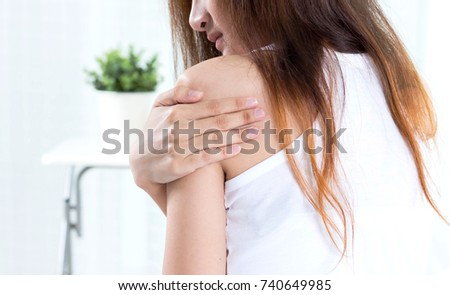 young suffering from shoulder pain in bedroom #740649985