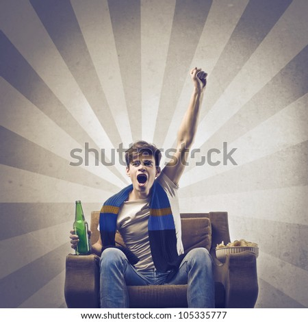 Young supporter triumphing on an armchair