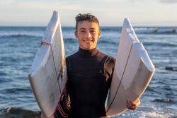 Young surfer comes out of the water carrying the broken board in the middle. Handsome guy with wetsuit. Horizon over the water