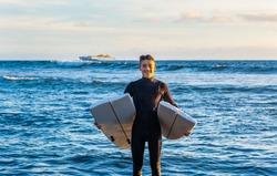 Young surfer comes out of the water with the board broken in half. Handsome guy with wetsuit. Horizon over the water and incoming ship.