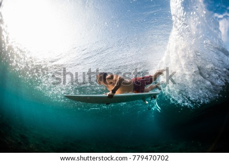 Young surfer dives under the ocean wave and performs trick named in surfing as a Duck Dive #779470702
