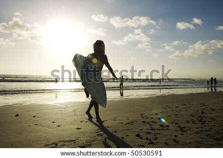 young surfer holding a surf board on the beach in Kuta, Bali, Indonesia