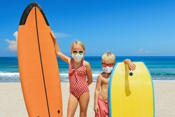 Young surfer kids with surf boards wear protective mask on sea beach. Cancelled cruises, tours due coronavirus COVID-19 epidemic. Travel ban for family vacation, tourism industry crisis at summer 2020