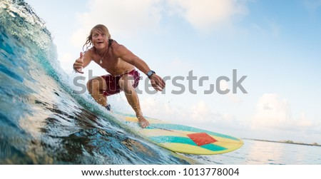 Young surfer rides ocean wave and shows the Shaka sign. Extreme sport and active lifestyle concept