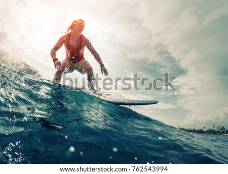 Young surfer rides the ocean wave. Extreme sport and action concept