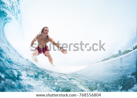 Young surfer rides the perfect tropical ocean wave. Extreme sport and active lifestyle concept. Surfspot named Jailbreak, Maldives