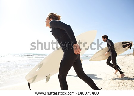 Young surfers sports men on a white sand beach carrying a surfing board and running into the sea  while on vacation during a sunny day, with an intense blue sky and light reflections in the water.