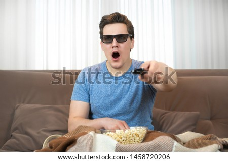 young surprised man wearing sunglasses watching movie eating popcorn clicking remote control #1458720206