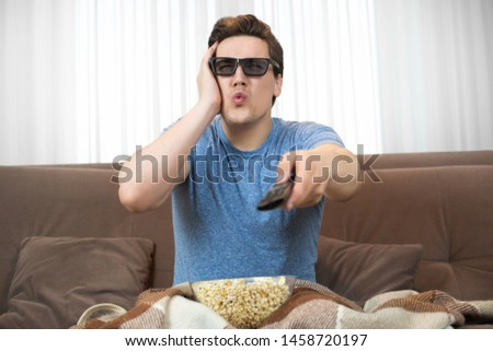 young surprised man wearing sunglasses watching movie eating popcorn clicking remote control looks astonished #1458720197