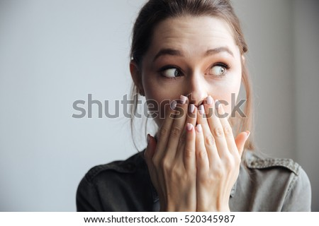 Young surprised woman in shirt looking away. covering her mouth. isolated gray background #520345987