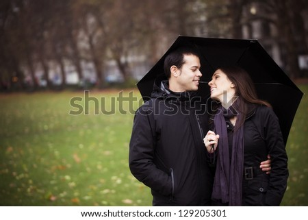 Young sweet couple sharing umbrella and smiling each other