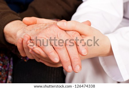 Young sweet doctor holds the old woman hands