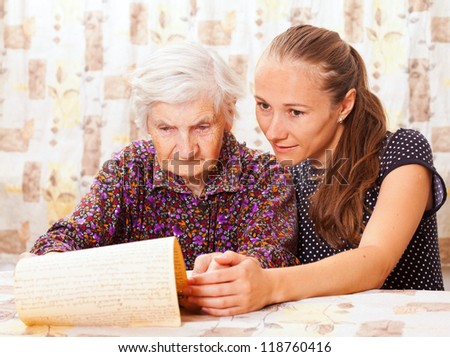 Young sweet lady holds the elderly woman\'s hand