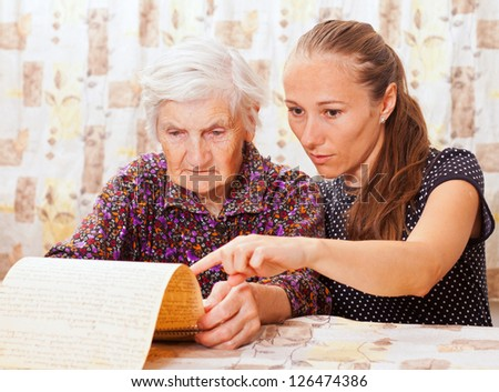 Young sweet lady holds the elderly woman's hand