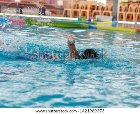 Young swimmer swimmer freestyle stroke in side the pool.   #1421989373