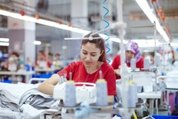 Young tailor seamstress working on textile factory