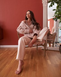Young tall slim stylish fashionable brunette woman sitting at armchair in terracotta interior. Elegant girl with long hair in beige jeans and jacket