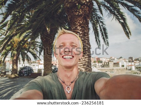 Young tanned guy shoots self-portrait in a background of palm trees