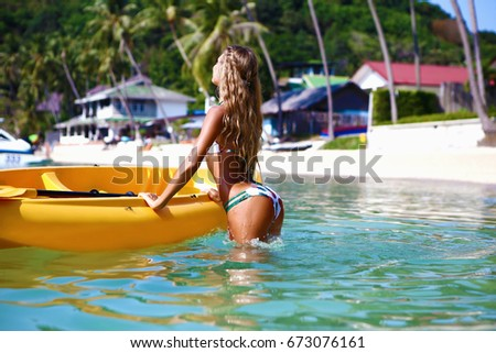 Young tanned woman on yellow kayak in the sea. A girl on a kayak floats on waves in the ocean #673076161