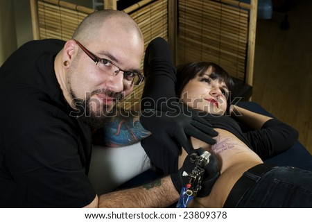 stock photo : Young tattoo artist tattooing happy client in tattoo shop