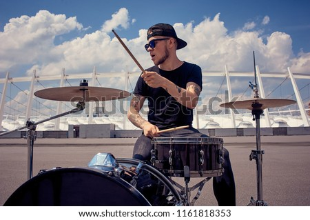 young tattooed drummer in sunglasses playing drums on street #1161818353