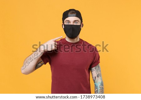 Young tattooed man guy in casual t-shirt cap posing isolated on yellow wall background studio portrait. People emotions lifestyle concept. Mock up copy space. Pointing index finger on black face mask