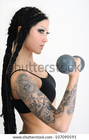 young tattooed stylish woman with dreadlocks,exercising with old dumbbells
