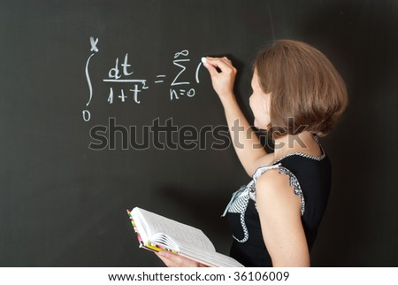 Young teacher is standing near blackboard in classroom