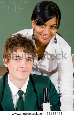 young teacher teaching high school student how to use microscope