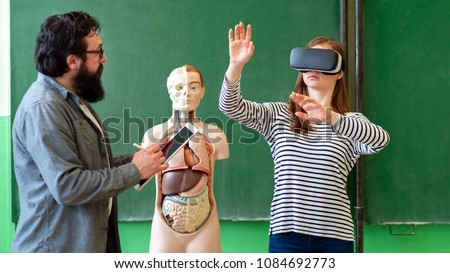 Young teacher using Virtual Reality Glasses and 3D presentation to teach students in biology class. Education, VR, Tutoring, New Technologies and Teaching Methods concept.