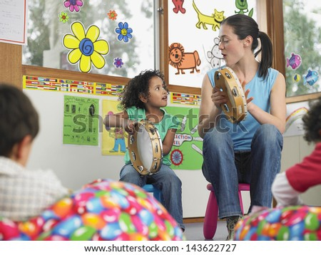Young teacher with girl playing music in classroom